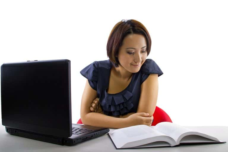 young Asian female studying with a computer and textbook